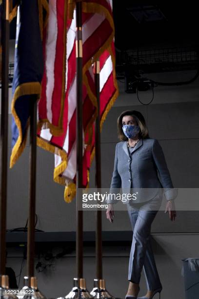 US House Speaker Nancy Pelosi a Democrat from California wears a protective mask while arriving to a news conference at the US Capitol in Washington...