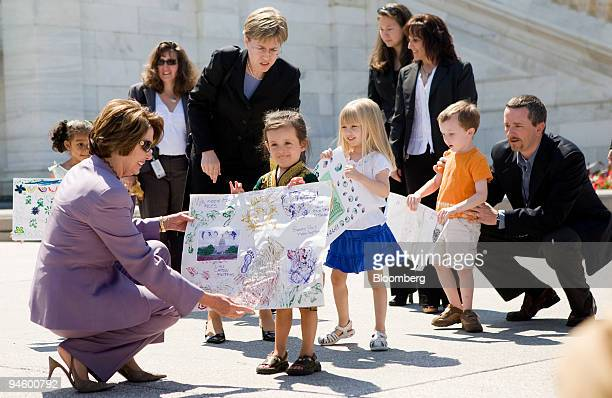 House Speaker Nancy Pelosi greets children of House employees who made drawings about the environment during a press conference on Capitol Hill June...
