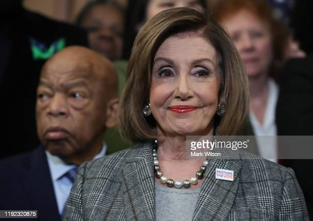 House Speaker Nancy Pelosi stands with Rep. John Lewis and other members during a news conference before the House votes on the H.R. 4, The Voting...