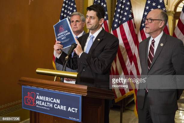 US House Speaker Paul Ryan a Republican from Wisconsin center holds up a copy of the American Health Care Act while Representative Greg Walden a...