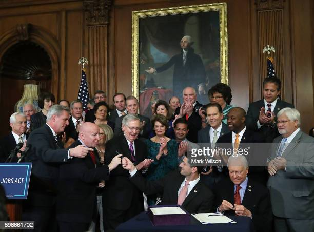 S House Speaker Paul Ryan flanked by Republican lawmakers gives House Ways and Means Chairman Rep Kevin Brady his pen after signing the enrollment...