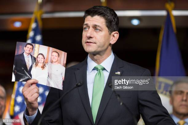 S House Speaker Paul Ryan holds up a photograph of himself with people in his district who have been affected by the opioid epidemic during a news...