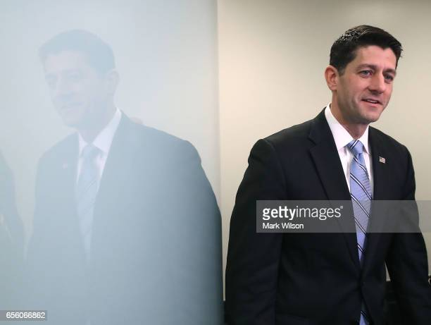 House Speaker Paul Ryan walks into a news conference after a House Republican closed party conference attended by US President Donald Trump on...