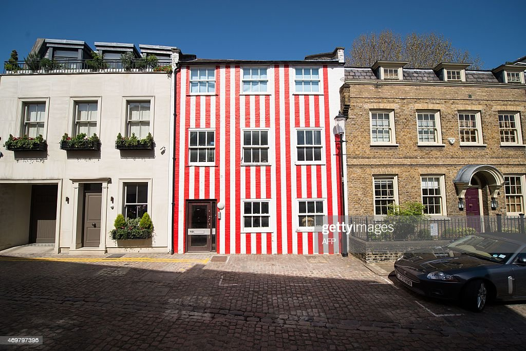 A house stands painted in red and white stripes in west London on April 15, 2015. A multimillion-pound house painted in garish candy stripes after a planning row has been branded hideous by neighbours. The townhouse underwent its unusual makeover after neighbours objected to plans to demolish the building and replace it with a new house and two-storey basement. NEAL