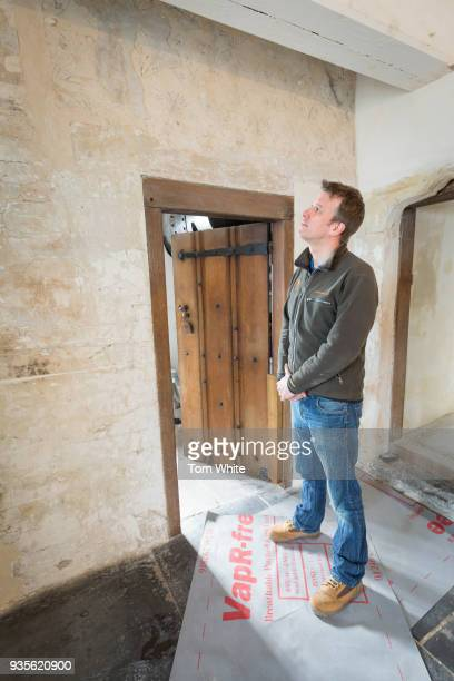 House steward Nick Lewis observes 16th century wall paintings that have been discovered in Lindisfarne Castle on March 21 2018 in Holy Island England...