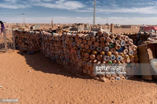 House under construction with plastic bottles filled with sand to build shelters that better withstand the climate of the country where temperatures...