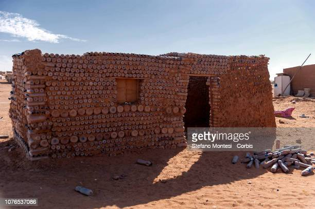 A house under construction with plastic bottles filled with sand to build shelters that better withstand the climate of the country where...