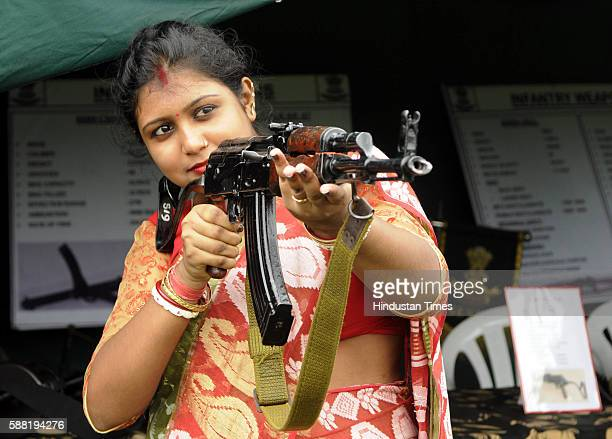 A house wife is trying to hold an AK47 rifle during 'Know Your Army' Exhibition at Saltlake SectV on August 10 2016 in Kolkata India