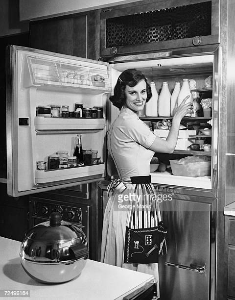 House wife removing milk from refrigerator