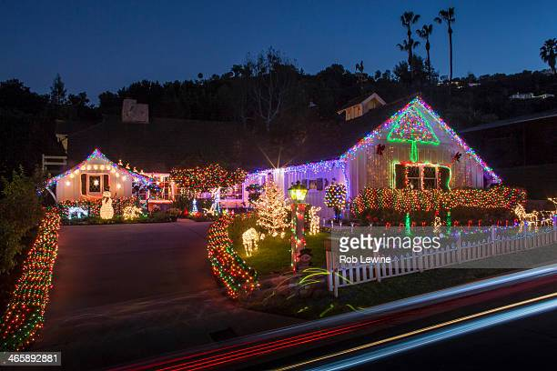 house with abundant exterior christmas lights - excess stock photos and pictures
