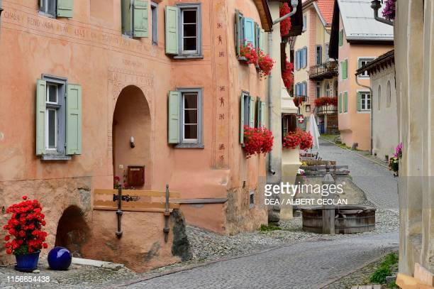 House with flowering geraniums on the windows in a street of the village, Guarda, Scuol, Engadin, Canton of Graubunden, Switzerland.