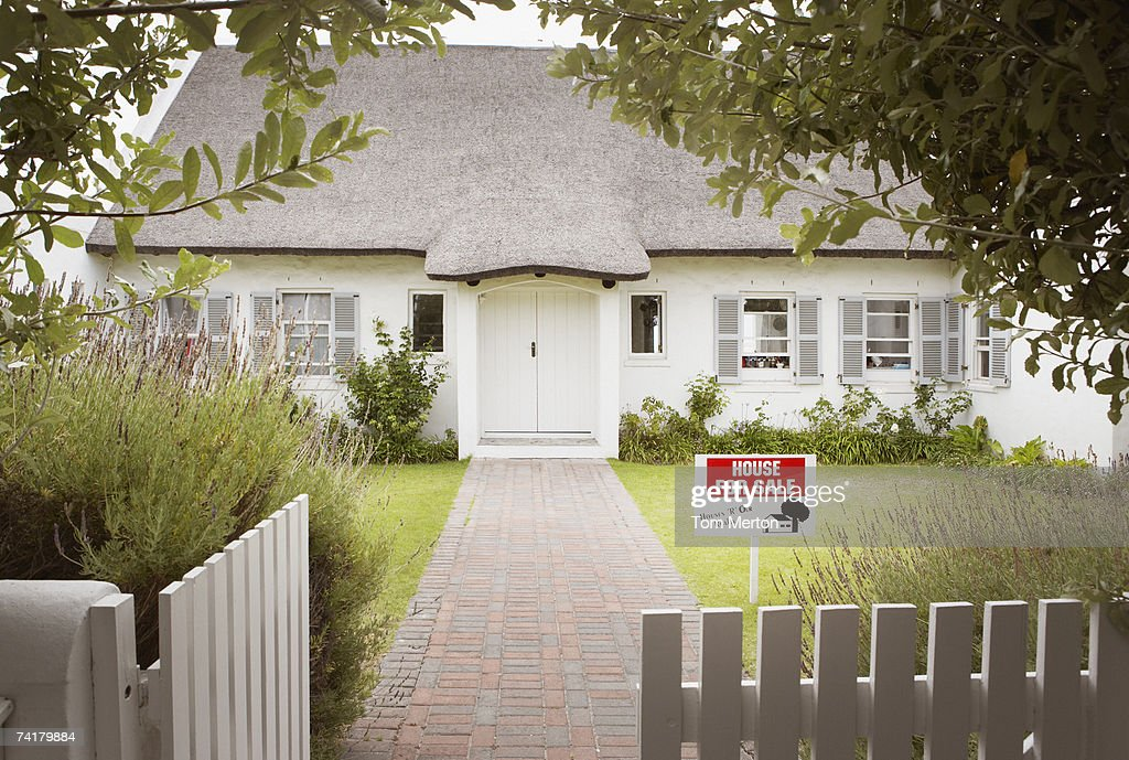 House with for sale sign in yard and open wooden fence : Stock Photo