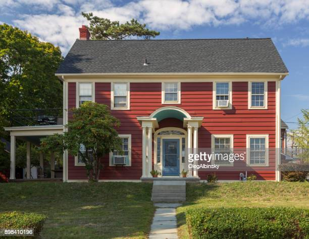 House with Red Clapboard Exterior, Green Trees, Shrubs and Blue Sky, Nyack, Rockland County, Hudson Valley, New York.