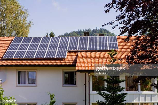 house with solar panels on the roof - solar energy dish stock pictures, royalty-free photos & images