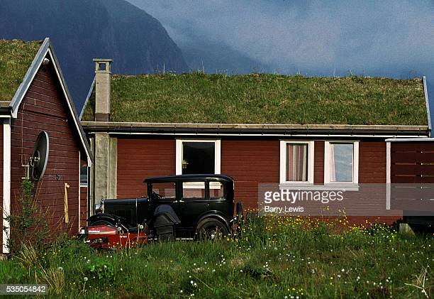 House with turf roof with car parked outside in Hustad. For more than a century, the coastal steamer Hurtigruten has been the lifeline linking the...