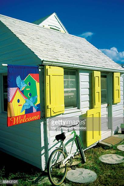 house with yellow shutters and bicycle parked outside, dunmore town, harbor island, bahamas - ダンモアタウン ストックフォトと画像