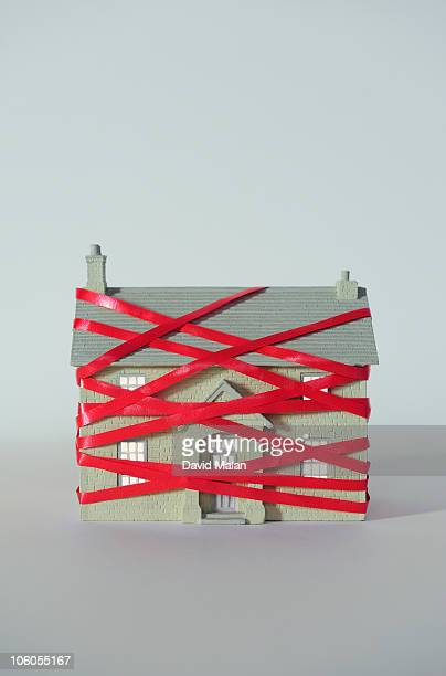 house wrapped in red tape. - bureaucracy stock pictures, royalty-free photos & images