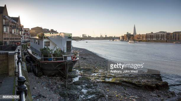 houseboat beached at low tide on the river thames in docklands, london - alternative lifestyle stock pictures, royalty-free photos & images