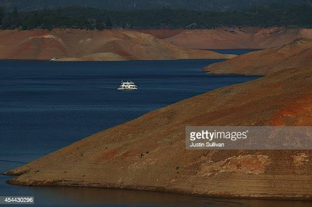 A houseboat is dwarfed by the steep banks of Shasta Lake on August 30 2014 in Redding California As the severe drought in California continues for a...
