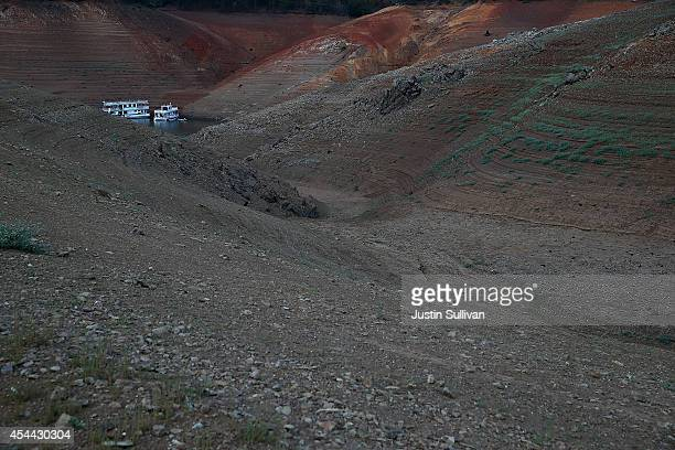 A houseboat is dwarfed by the steep banks of Shasta Lake on August 30 2014 in Lakehead California As the severe drought in California continues for a...