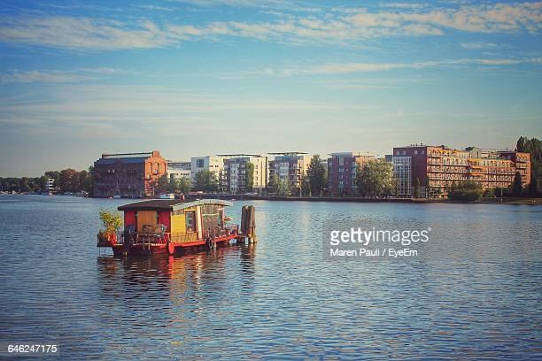 houseboat sailing in river against sky - houseboat stock pictures, royalty-free photos & images