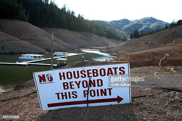 Houseboats are dwarfed by the steep banks of Shasta Lake at Holiday Harbor on August 30 2014 in Lakehead California As the severe drought in...