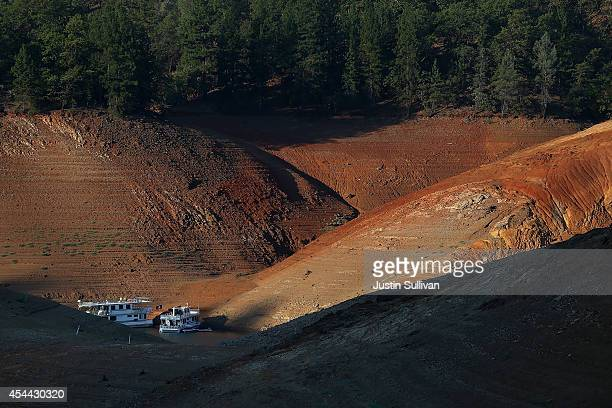 Houseboats are dwarfed by the steep banks of the Shasta Lake near Packers Bay Marina on August 30 2014 in Lakehead California As the severe drought...