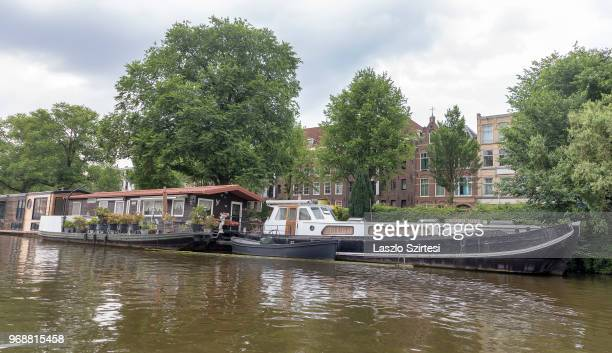 Houseboats are moored on the Nieuwe Vaart Canal on May 30 2018 in Amsterdam Netherlands Houseboats of Amsterdam are provided with all conveniences...