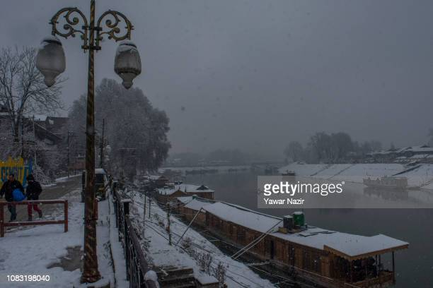 Houseboats are moored to the bank of Jehlum river during fresh snowfall on January 16 2019 in Srinagar the summer capital of Indian administered...