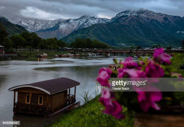 Houseboats are moored to the bank of river Jehlum in front the snow capped mountains on April 20 2018 in Srinagar the summer capital of Indian...