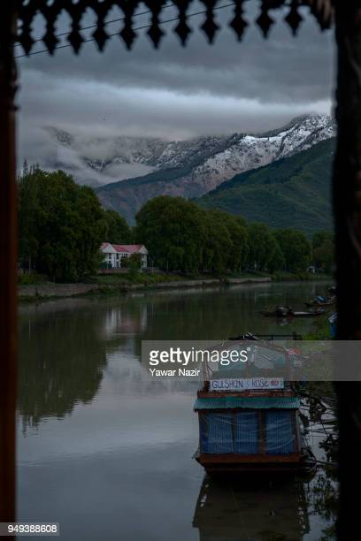 Houseboats are moored to the bank of river Jehlum in front the snow capped mountains on April 22 2018 in Srinagar the summer capital of Indian...