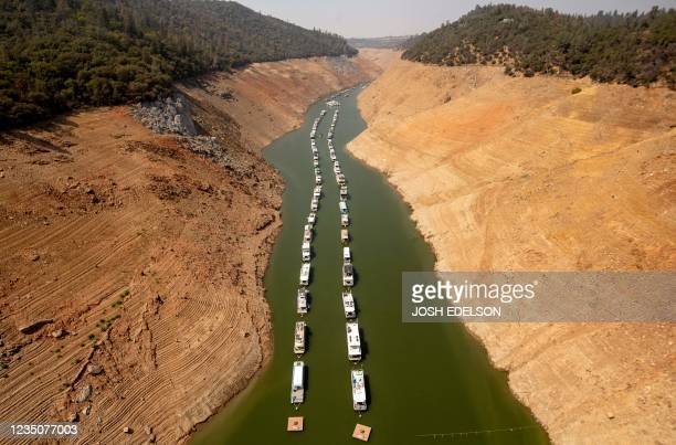 Houseboats sit in a narrow section of water in a depleted Lake Oroville in Oroville, California on September 5, 2021. - Lake Oroville is currently at...
