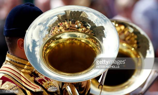 Household Cavalry guards and band members are reflected in a tuba during a parade following the Order of the Garter Service at St George's Chapel in...