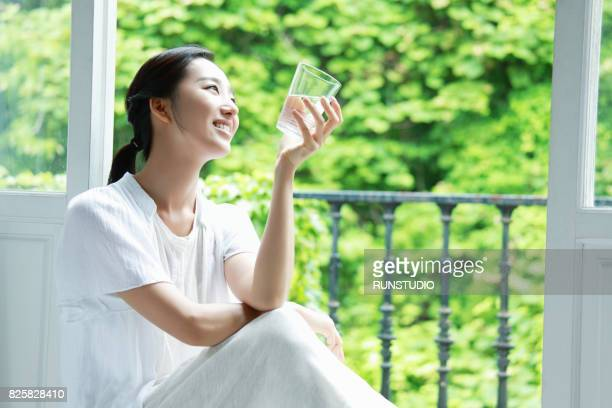 household housewife resting holding a water cup at the window - 心の平穏 ストックフォトと画像