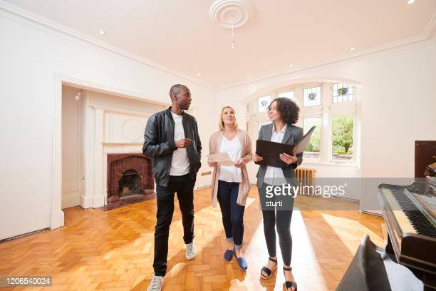 househunt couple with agent - real estate agent stock pictures, royalty-free photos & images