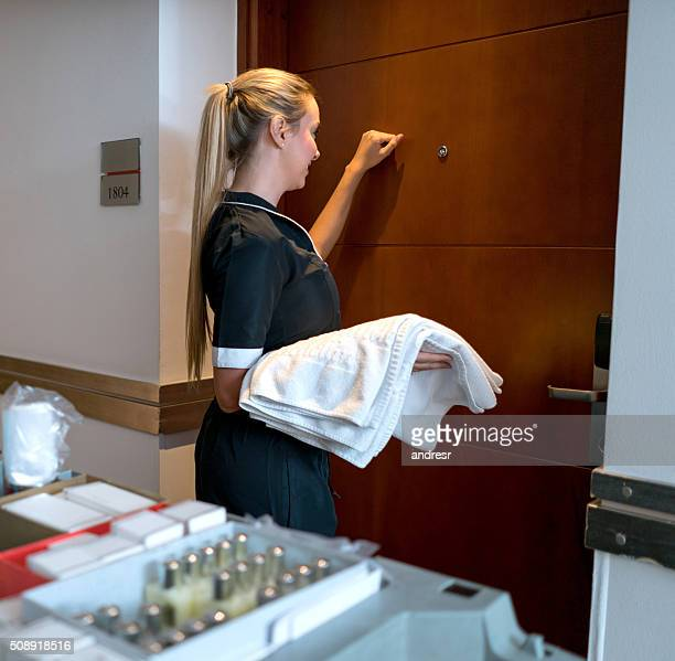 housekeeper knocking on a door at the hotel - knocking on door stock photos and pictures