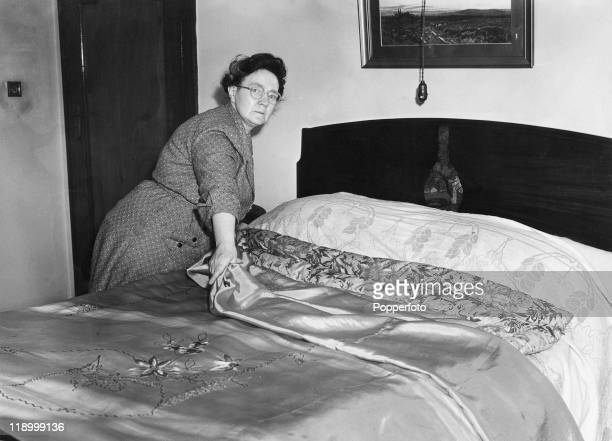 Housekeeper Louisa Merrifield makes the bed in the Blackpool bungalow in which her employer Sarah Ann Ricketts was found poisoned July 1953...