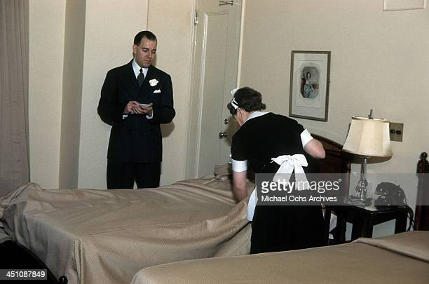 A housekeeper makes a twin bed in a guest room as a supervisor inspects the work in The Plaza Hotel in New York New York