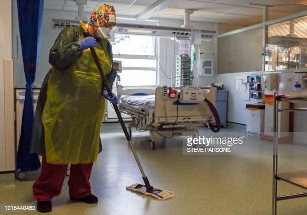 A housekeeper wearing full PPE including a face mask long apron and gloves as a precautionary measure against COVID19 works to clean an Intensive...