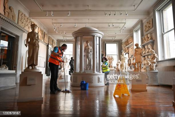 Housekeeping staff clean in the Sculpture Room of the Walker Art Gallery in Liverpool, north west England on May 13 as National Museums Liverpool...