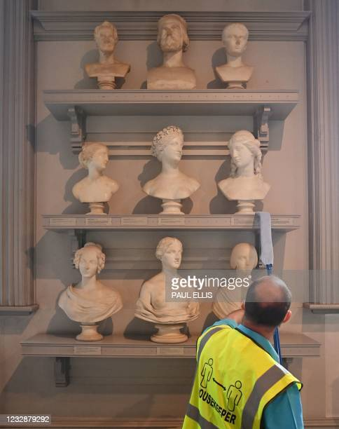 Housekeeping staff member dusts an exhibit in the Sculpture Room of the Walker Art Gallery in Liverpool, north west England on May 13 as National...