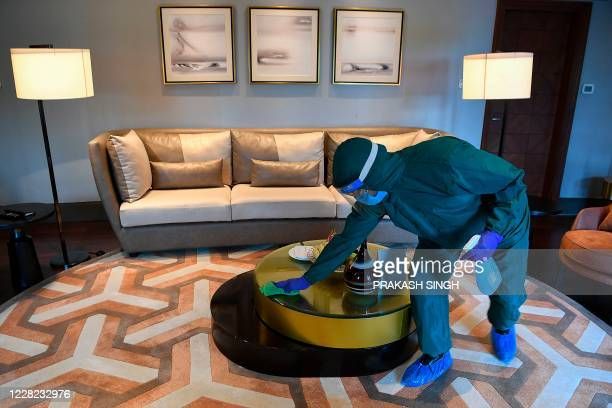 Housekeeping staff of Taj Palace hotel wearing personal protective equipment cleans and sanitizes a room in New Delhi on August 28, 2020.