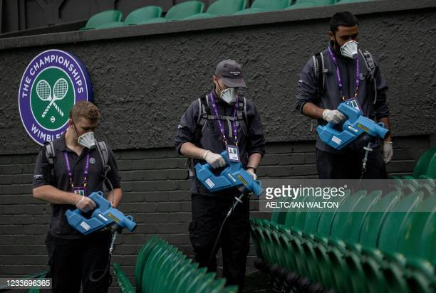 Housekeeping Staff use a mist spray to disinfect the seats on Centre Court ahead of the first day of the Wimbledon Championships at The All England...