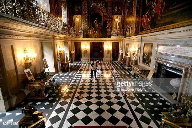 Housemaid Kath Watts poses during her cleaning routine as she Spring cleans the floor of The Painted Hall in the magnificent Chatsworth House home of...