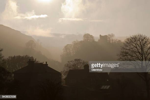 houses afore misty landscape with english castle - peveril castle stock pictures, royalty-free photos & images