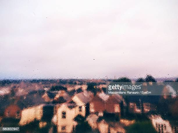 houses against sky seen through wet glass window - massimiliano ranauro stock pictures, royalty-free photos & images