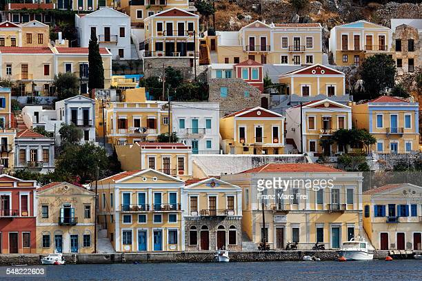 houses along the harbour quay of yialos, symi - symi stock photos and pictures