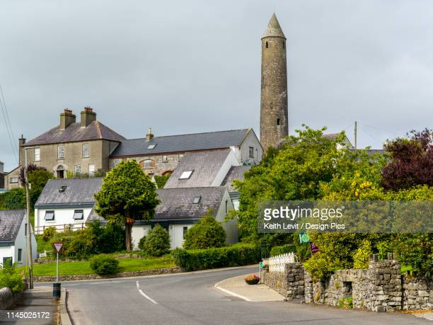 houses and a stone round tower in killala town - irish round tower stock photos and pictures