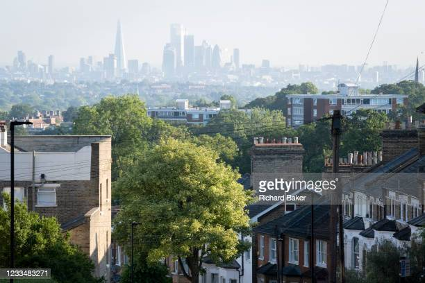 Houses and flats with an elevated viewpoint of the London skyline at Crystal Palace, on 16th June 2021, in London, England.