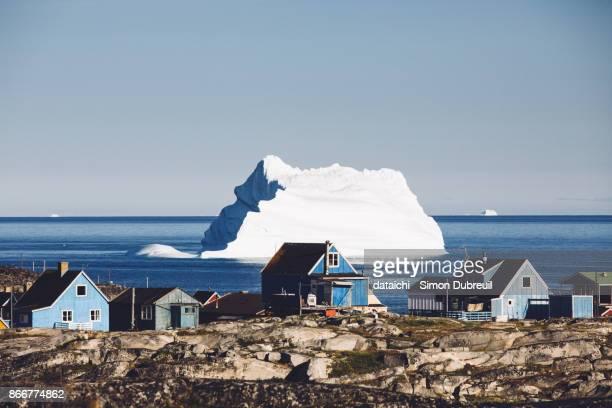houses and iceberg in qeqertarsuaq - grönland stock-fotos und bilder
